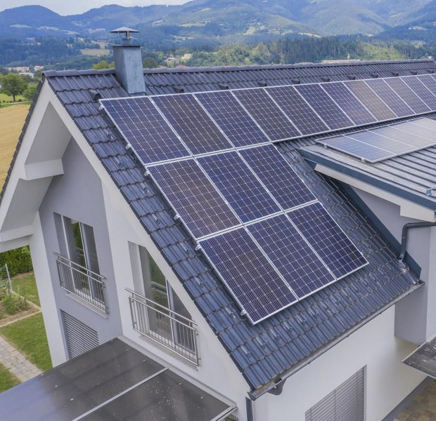 A high angle shot of a private house situated in a valley with solar panels on the roof
